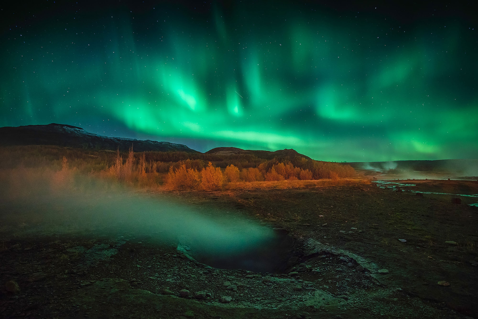 iurie belegurschi sony alpha 7RIII the aurora borealis dances above distant mountains while a foreground geyser is illuminated green