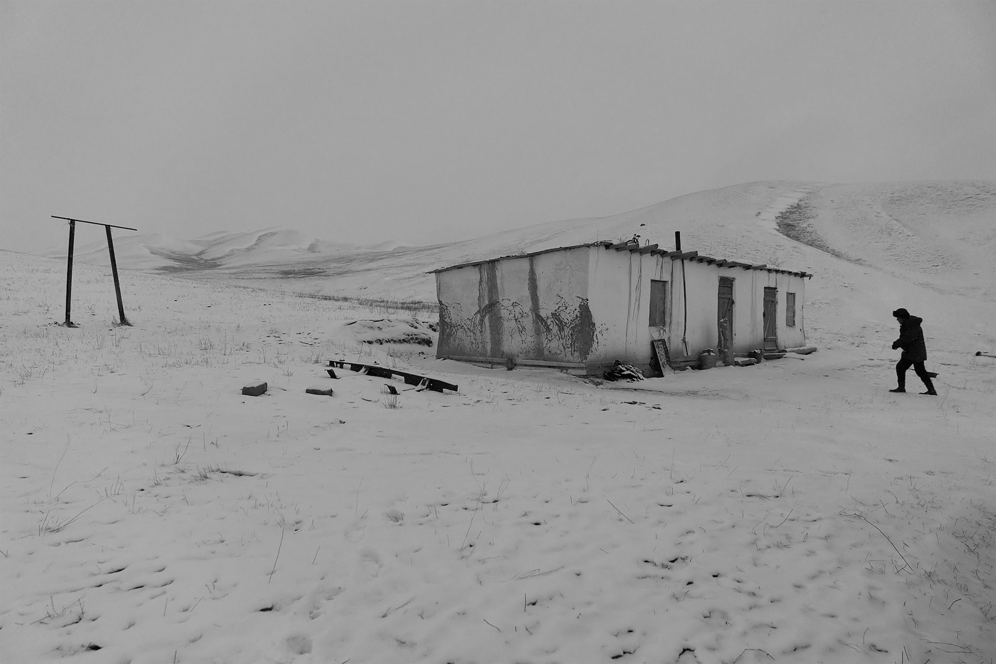 frederik buyckx sony alpha 7RM3 shepherd trudges towards a run down shack in the snowy mountains