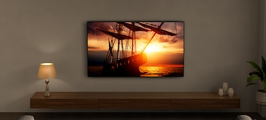 TV hanging on a wall showing a ship at sunset