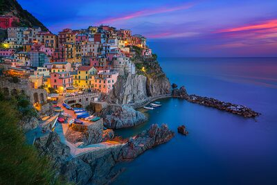 albert dros sony alpha 7RII a colourful harbour town at dusk with the sky striped with red clouds as the sun sets jpgmanarola Sony24 70GM A7RII