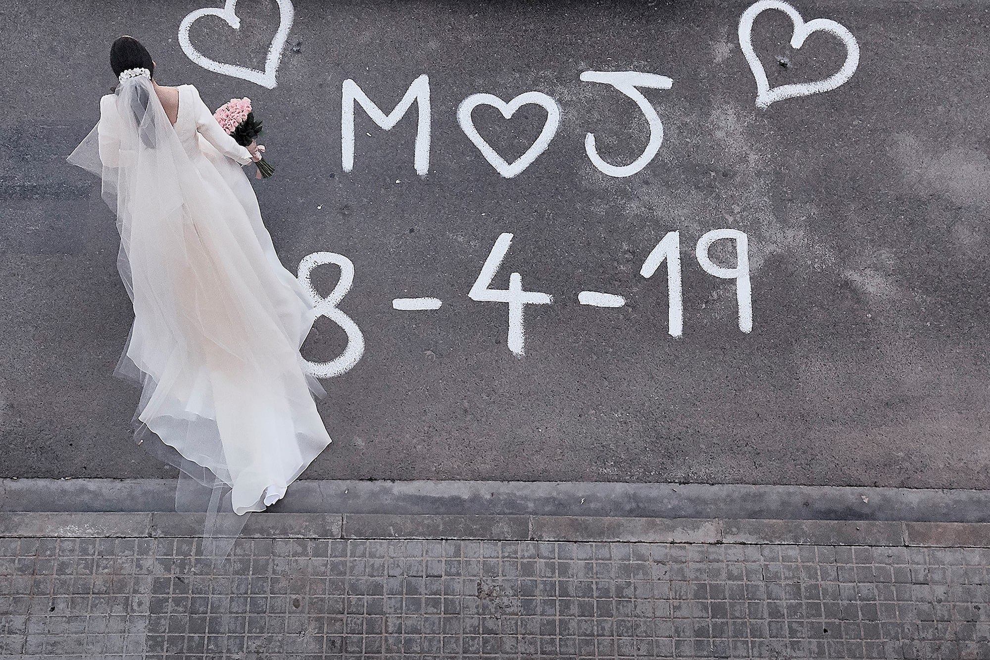 jorge miguel jaime baez sony RX0 birds eye shot of a bride crossing the road with the wedding date scrawled on the road