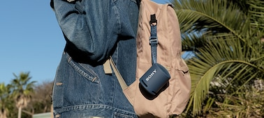 Image of the XB13 EXTRA BASS(TM) Portable Wireless Speaker attached to a young woman's backpack.