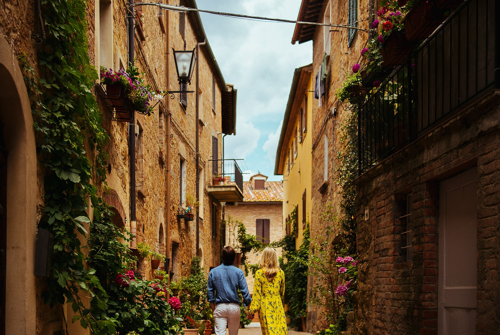 George Kasionis Stam Tsopanakis sony alpha 7m3 view from the back of a couple walking in a flowered street in tuscany