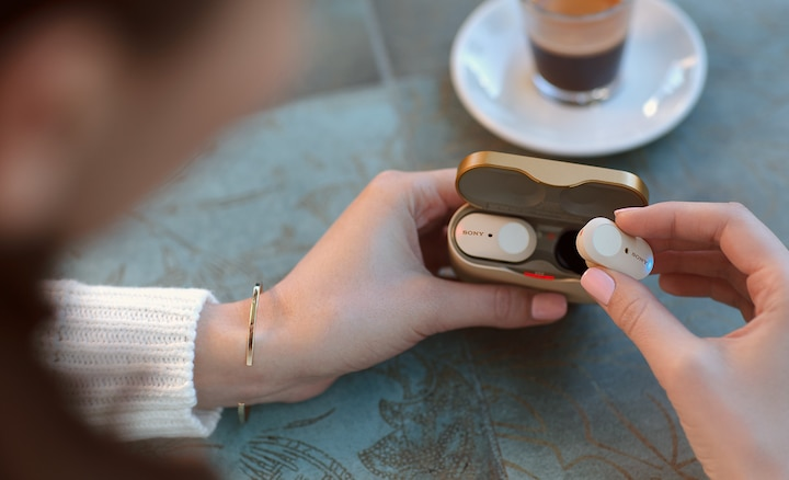 Lifestyle image showing WF-1000XM3 earbuds being placed into magnetic charging case.