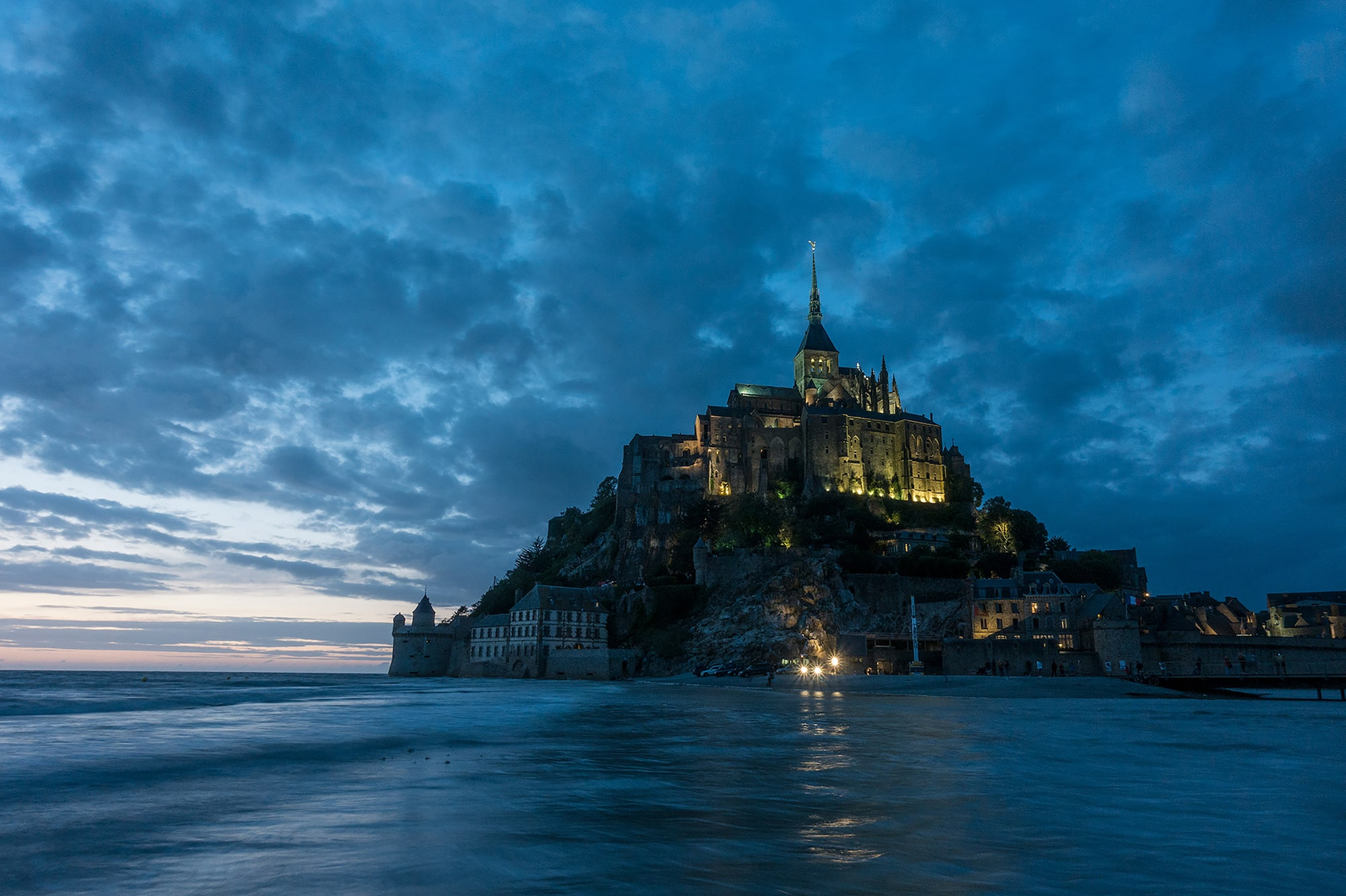 marek arcimowicz sony rx100V a castle looms against a dark cloudy sky with the ocean in the foreground