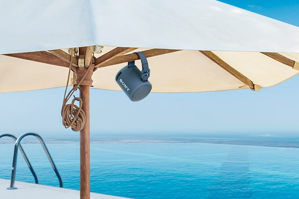 Image of the XB13 EXTRA BASS(TM) Portable Wireless Speaker attached to a parasol on a tropical beach.