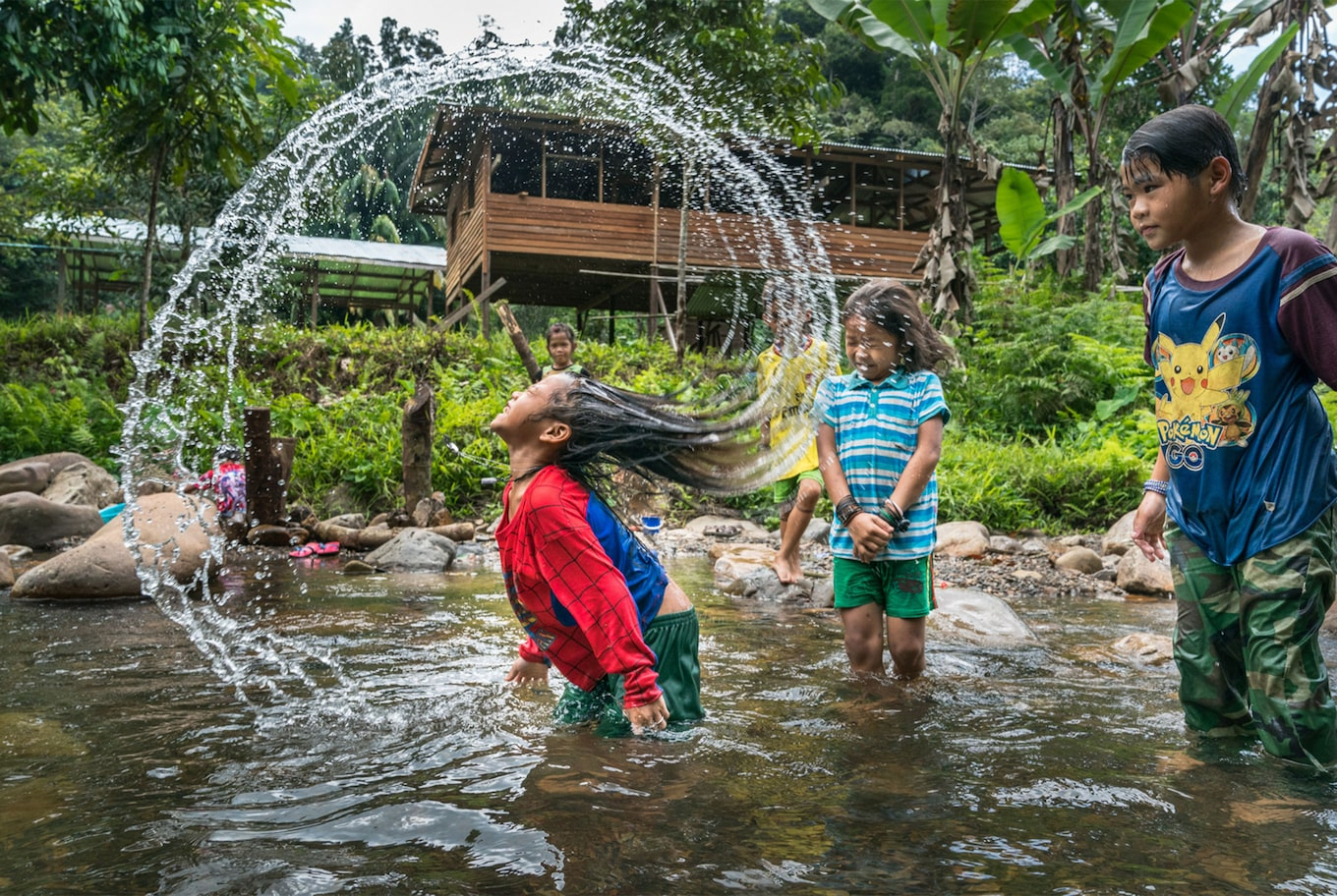 Tomas Wuethrich sony alpha 9 children larking about in a jungle pond with a girl sshaking her wet hair