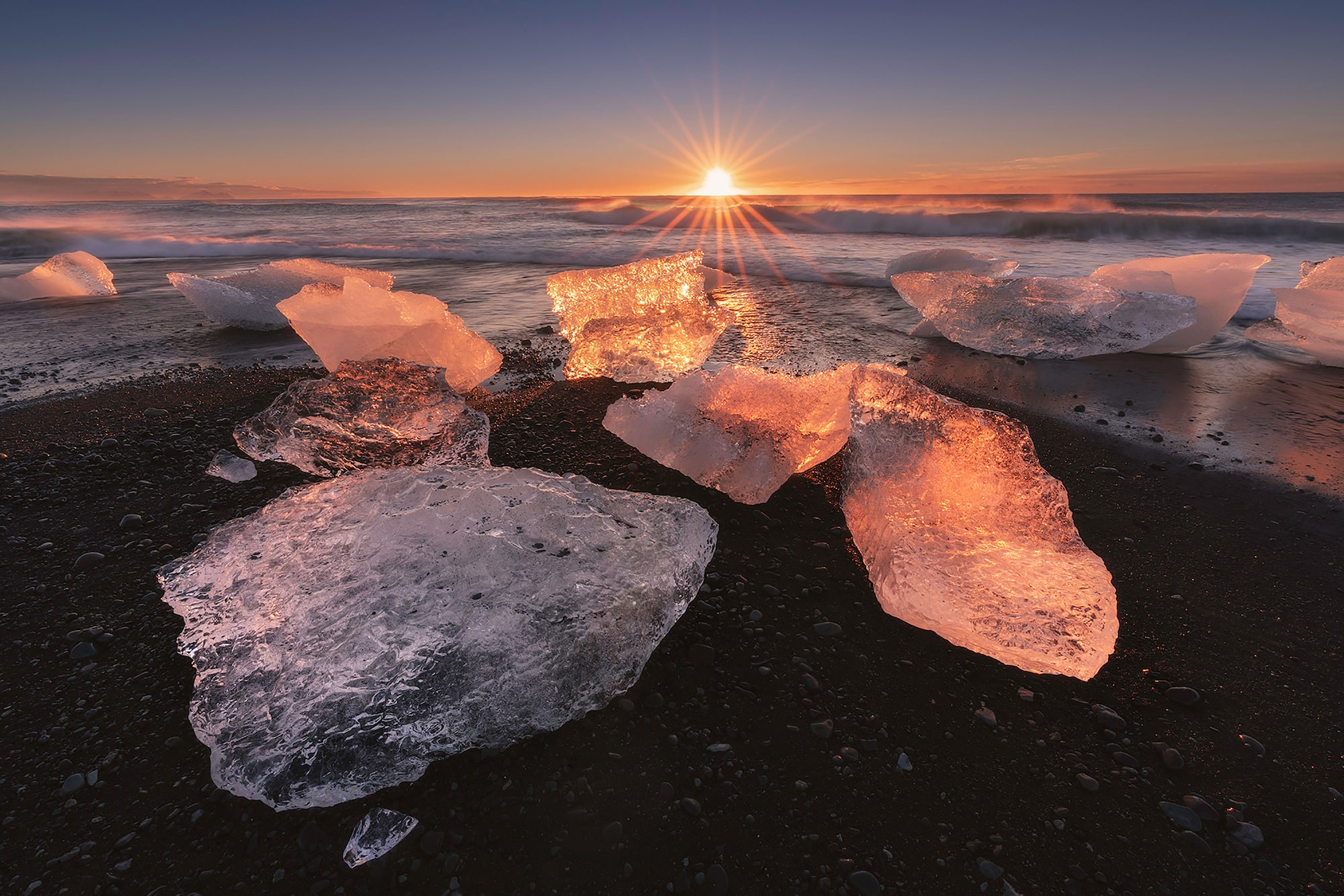 iurie belegurschi sony alpha 7RIII the sun rises on the horizon at the shore with large ice blocks illuminated in the foreground