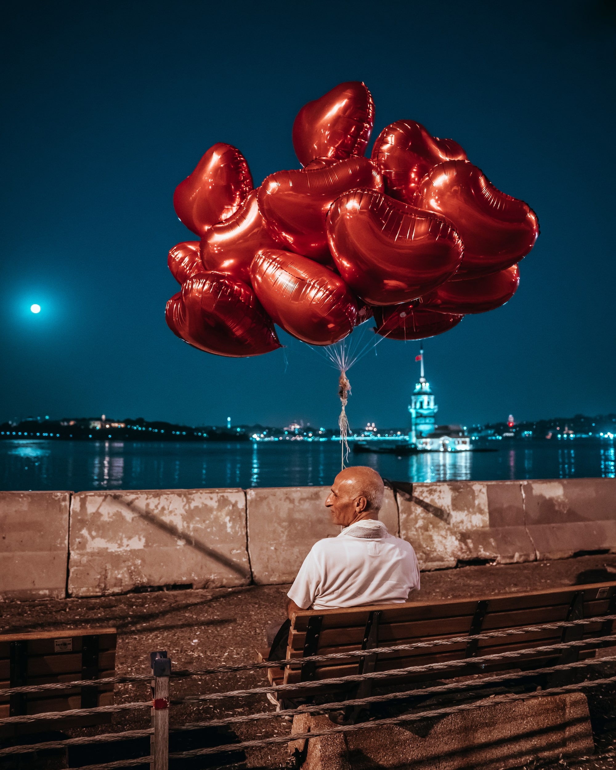 İlkin Karacan Karakus sony A7RM2 seated man holding a bunch of red heart balloons