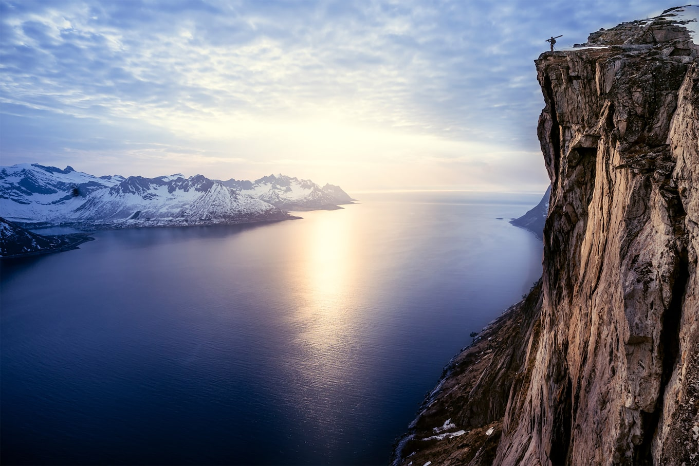 Daniel Ronnback sony alpha 9 skier stands on the edge of a cliff with a sea and mountains landscape