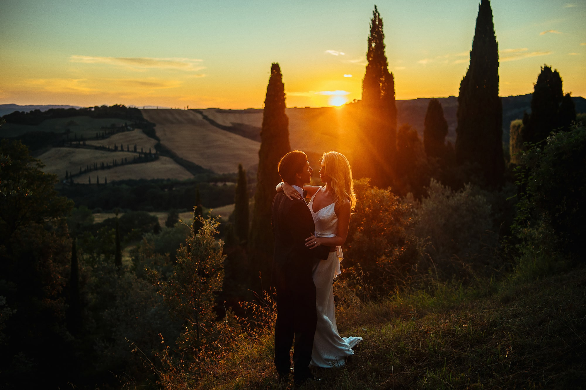 George Kasionis Stam Tsopanakis sony alpha 7m3 bride and groom hold one another in a tuscan field in front of the sunset