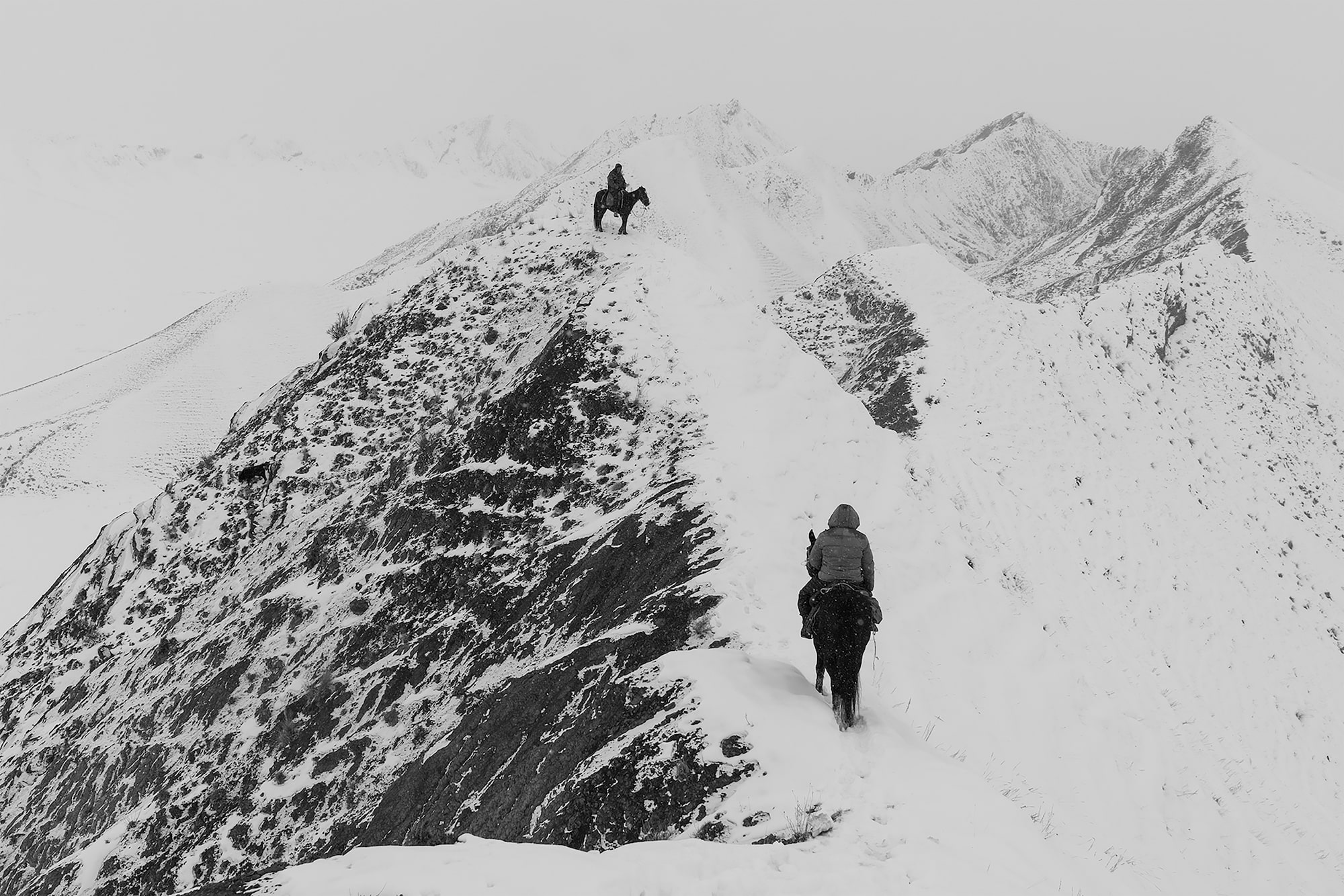 frederik buyckx sony alpha 7RM3 horseback shepherd makes his way up a mountain pass towards another shepherd