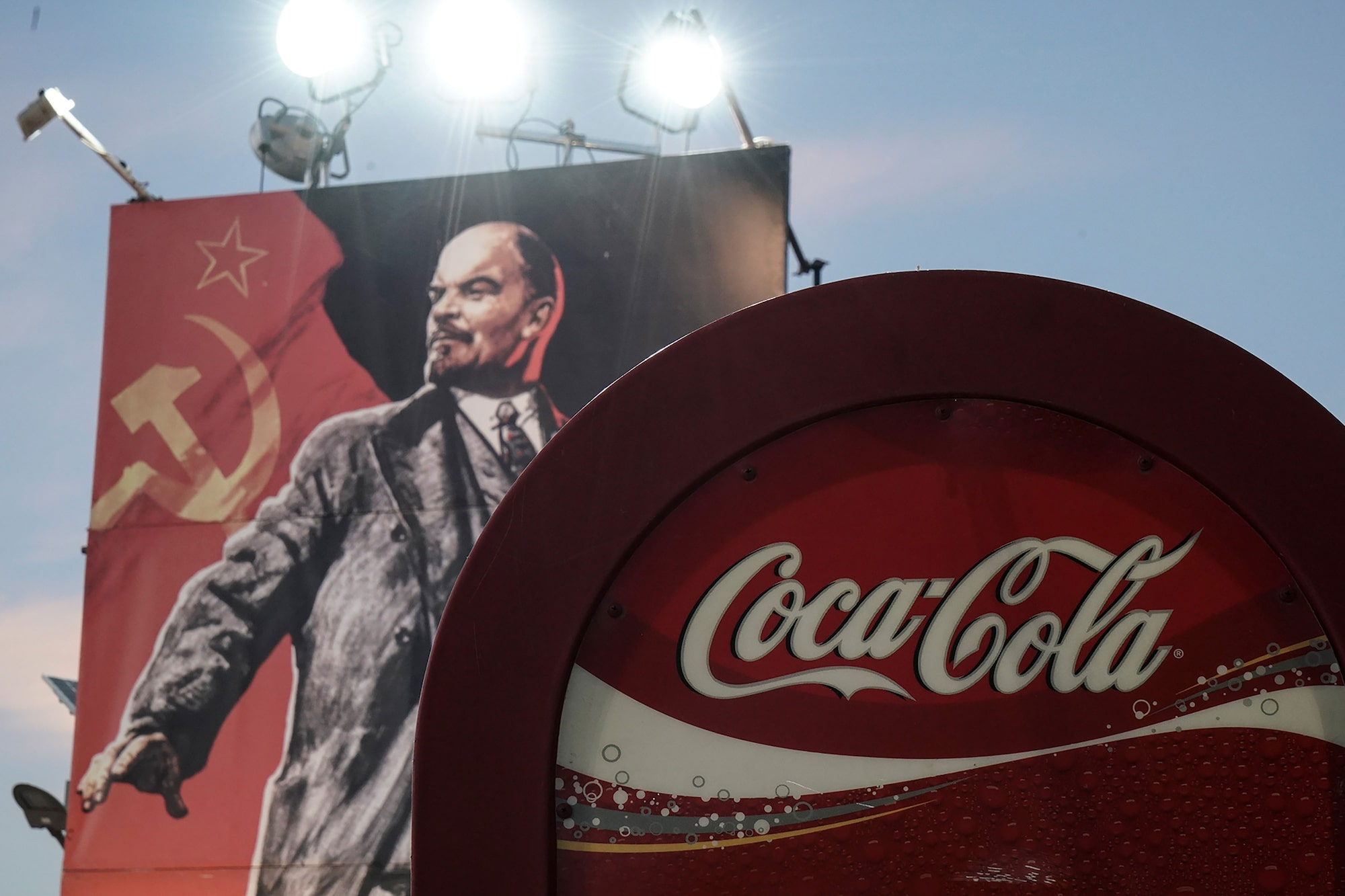 menelaos myrillas sony alpha 9 portrait of lenin behind a coca cola sign