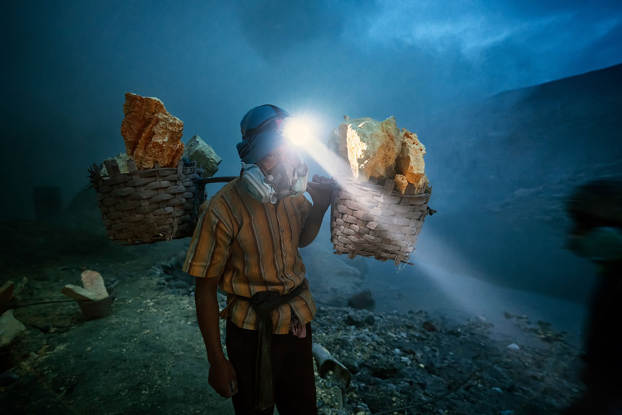 andrea frazzetta sony alpha 7RII miner with headtorch carries 2 baskets of sulphur rocks