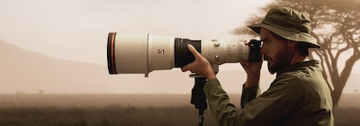 Image of a man looking through a tripod-mounted camera that is attached to a super-telephoto lens
