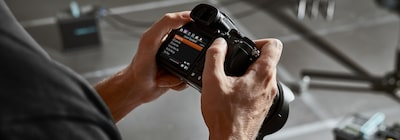 View of the back of the hand-held camera, showing a menu screen in the camera's monitor