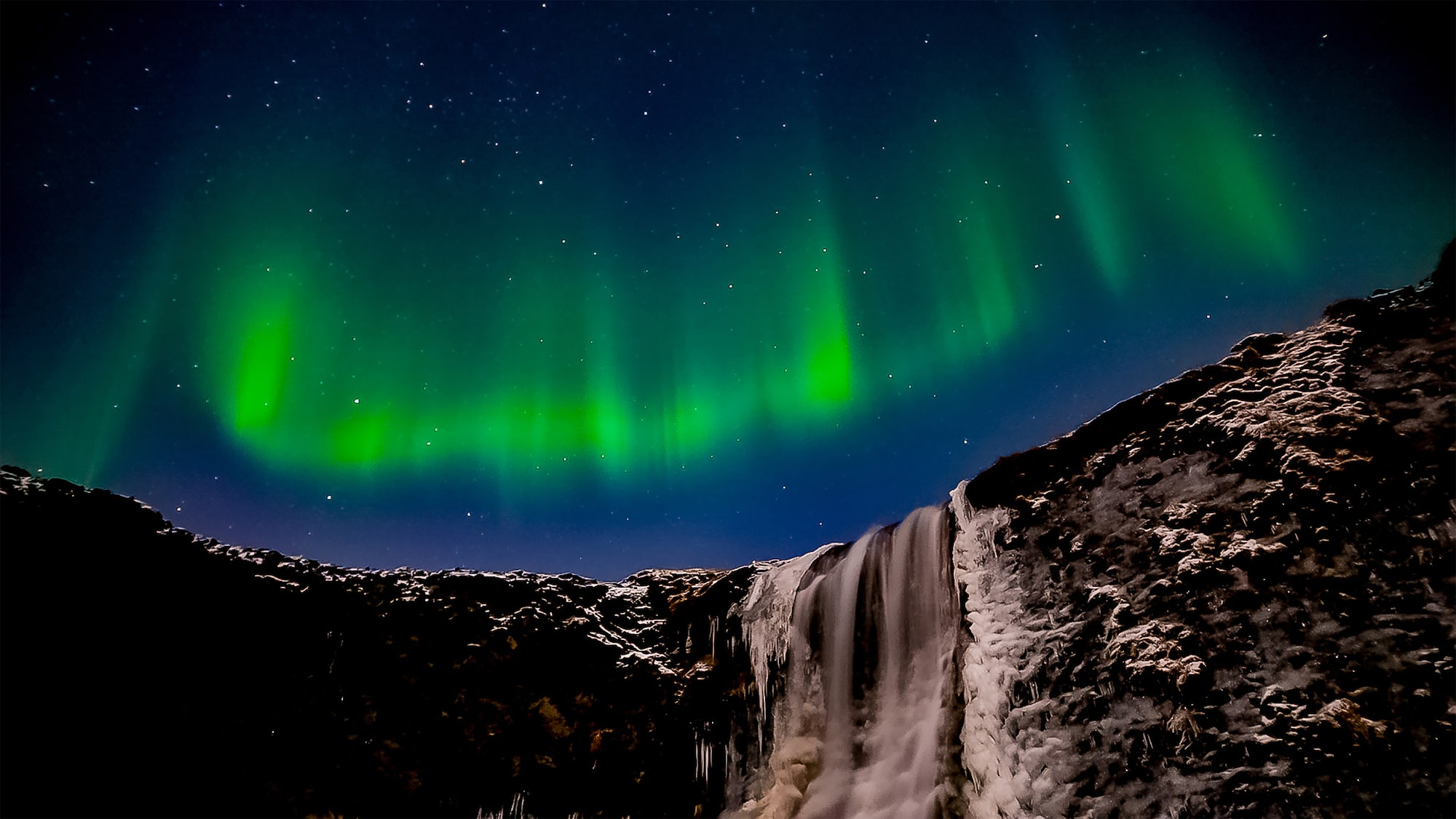 steve collins sony alpha 7SII intense green aurora light dances over a waterfall in iceland