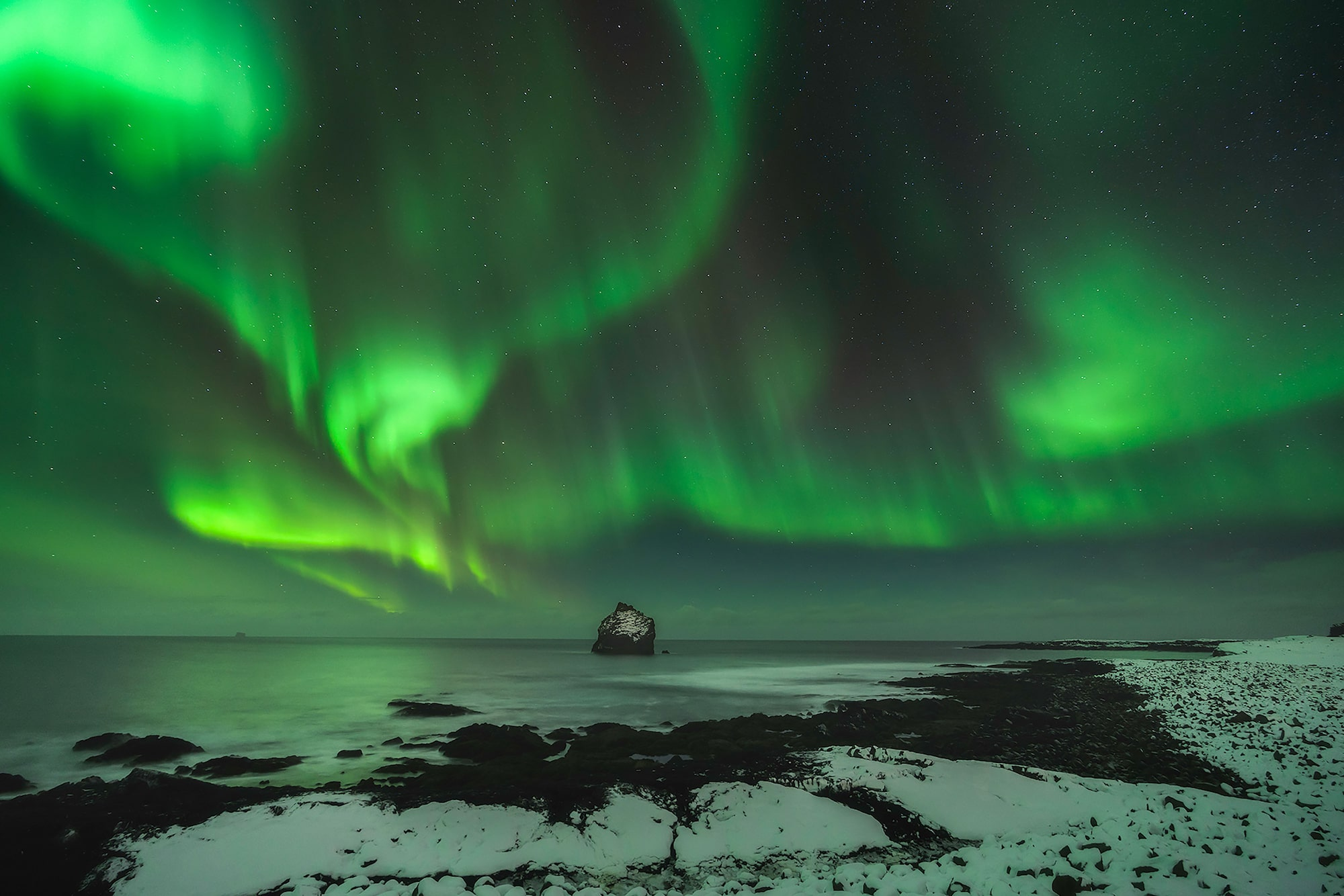 iurie belegursch sony alpha 7RIII aurora borealis at the shore with a large snowy rock n the distance