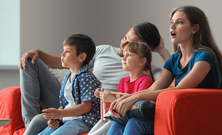 Family watching TV from a sofa